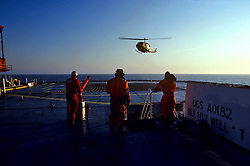 Stock photo of a helicopter landing on a rig in the ocean