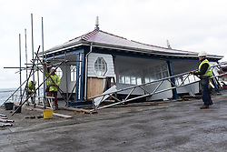 © Licensed to London News Pictures. 09/01/2014. Aberystwyth, UK Scaffolding contractors begin the work of encasing the historic public shelter on Aberystwyth promenade, which was virtually destroyed in the recent storms, in a  safety cage before the work of carefully dismantling it can begin.  Because it is a listed building, CADW,  the Welsh Government's historic environment service,  is keen to preserve as much of the original structure as possible. Photo credit : Keith Morris/LNP