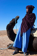 Young man in traditional cloth with dromedary against blue sky.