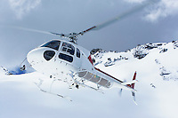 Helicopter flying over snowy mountain peaks