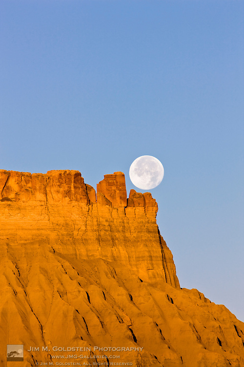 A full moon sets over Factory Butte at sunrise in the desert of southwestern Utah