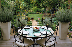 Raised deck seating and dining area surrounded by tall ceramic containers of Lavender - Lavandula dentata. Mosaic circular table with wrought iron chairs.Design: Anthony Goff