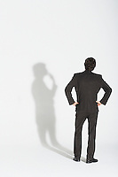 Young businessman standing hands on hip arguing with own shadow back view