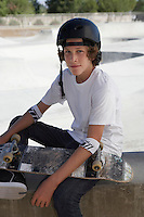 Teenage boy (16-17) with skateboard at skateboard park portrait