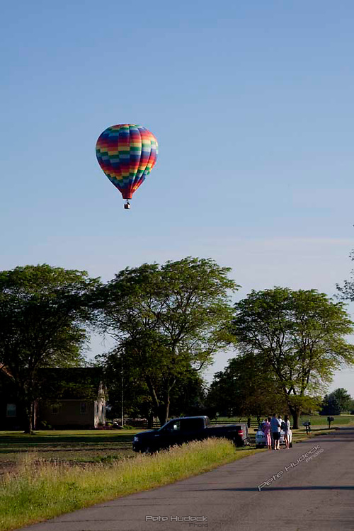 A family stops along side the road to view a hot air balloon