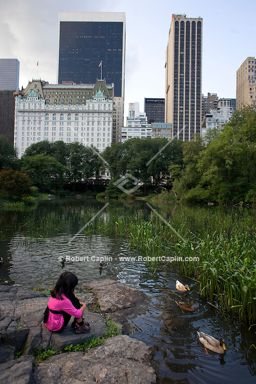 Charlotte McCarron, 7, feeds the ducks in The Pond in Central Park in New York. Sept. 30, 2008.