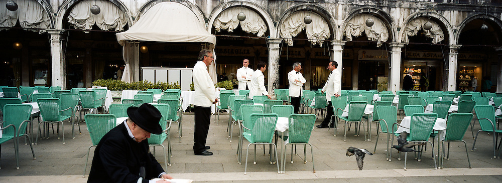 An artist paints in the Piazza San Marco as waiters wait for customers in Piazza San Marco. Venice, Italy. 1st May 2011. Photo Tim Clayton
