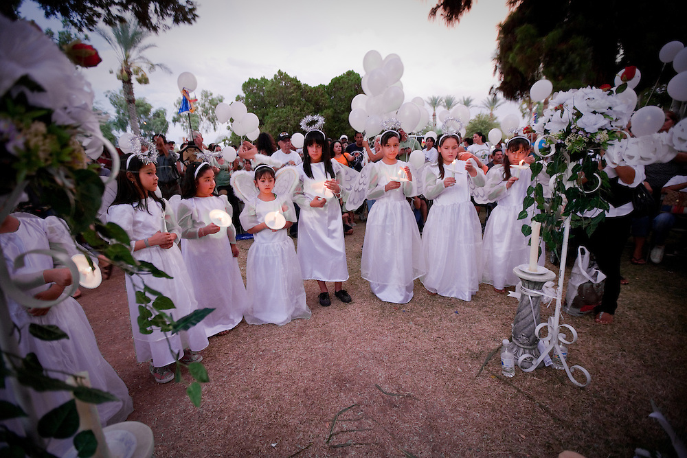 Girls wearing angel wings, halo, and white dresses, lead the candle light vigil in front of the State Capitol in Phoenix.