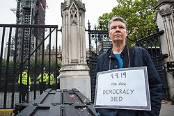 "London, UK. 11 September, 2019. A pro-Remain protester outside Parliament wears a sign reading ""9.9.19 The Day Democracy Died"" in reference to the proroguing of Parliament by Prime Minister Boris Johnson's Government."