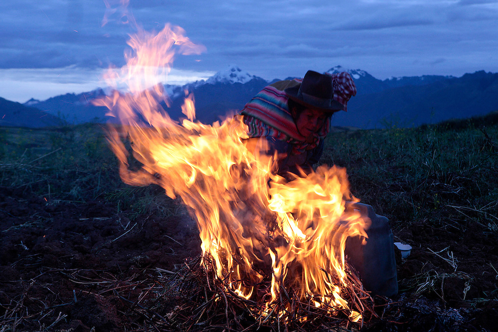Indigenous woman on fire heated a container of corn chicha in Chincheros, Cuzco, Saturday, June 4, 2011. (AP Photo/Esteban Felix)