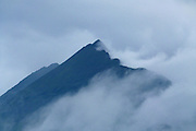 The dramatic jagged peak and knife-edge east ridge of Gars-bheinn enveloped in low cloud during a rain storm, photographed from Port Elgol, Isle of Skye. Gars-bheinn is the southern-most peak of the Cuillin Ridge, sometimes referred to as the Black Cuillin because of the dark grey colour of the Gabbro rock of which they consist.<br />