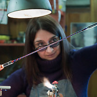 """VENICE, ITALY - DECEMBER 18:  Elena Rosso a glass  artist in Murano twists glass rods to make a """"zanfirico"""" cane on December 18, 2010 in Venice, Italy. There are only few female glass artists is Italy and they face continuous challanges in a traditionally male dominated field."""