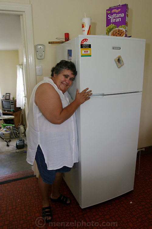 (MODEL RELEASED IMAGE). Marge Brown hugs her beloved refrigerator in the kitchen of her rented home in Riverview, Australia (near Brisbane). While the Browns are used to living with a nearly-empty refrigerator, they look forward to the days when it's full. Every two weeks a new check appears and the family goes to the supermarket. (Supporting image from the project Hungry Planet: What the World Eats.)