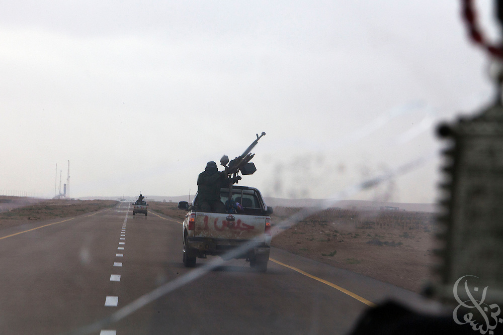 Opposition rebels drive technicals forward on the offensive on a highway outside the Libyan coastal oil town of Ras Lanouf, Libya March 05, 2011. Rebel forces shot down the fighter with anti-aircraft guns during their offensive toward Sert, killing the two pilots inside. .