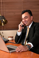 Hispanic executive having a phone conversation in his office.