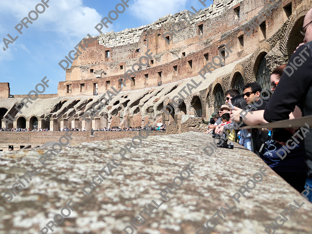 Low angle view of tourists inside of the Colosseum during the day with cameras