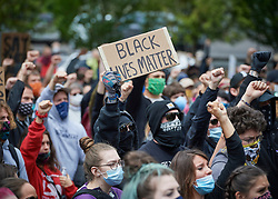 Many carrying signs, people participate in a June 7, 2020, Black Lives Matter protest in Eugene, Oregon. Participants protested the murder of George Floyd and other African-Americans by police. Most protesters wore masks because of the coronavirus pandemic.