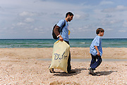 Israel Beach cleaning. Volunteers scan a beach collecting garbage