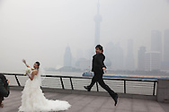 China, Shanghai. shooting chinese wedding on the Bund promenade, man jumping on a ball