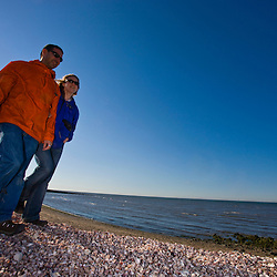 A young couple watches for wildlife on the shell covered sands of Long Beach in Stratford, Connecticut.  adjacent to the Great Meadows Unit of McKinney National Wildlife Refuge.