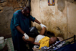 A woman waits to give birth at the home of a midwife in Mathare, a poor slum in Nairobi, Kenya.  Most women in Mathare can not afford to go to a hospital to give birth; they can not even afford the 10 minute taxi ride to get there.  The expecting mothers have no prenatal care and arrive to the midwives' homes once labor has already begun.  The midwives have no supplies and are usually have no formal training.  The mothers often give birth on dirt floors with no medicine, and their babies' unbilical cords are cut with dirty scissors and they are washed with tap water.