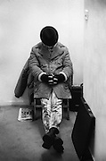 Neville sitting on a chair with portfolio case, Camden Market, London, UK, 1980s