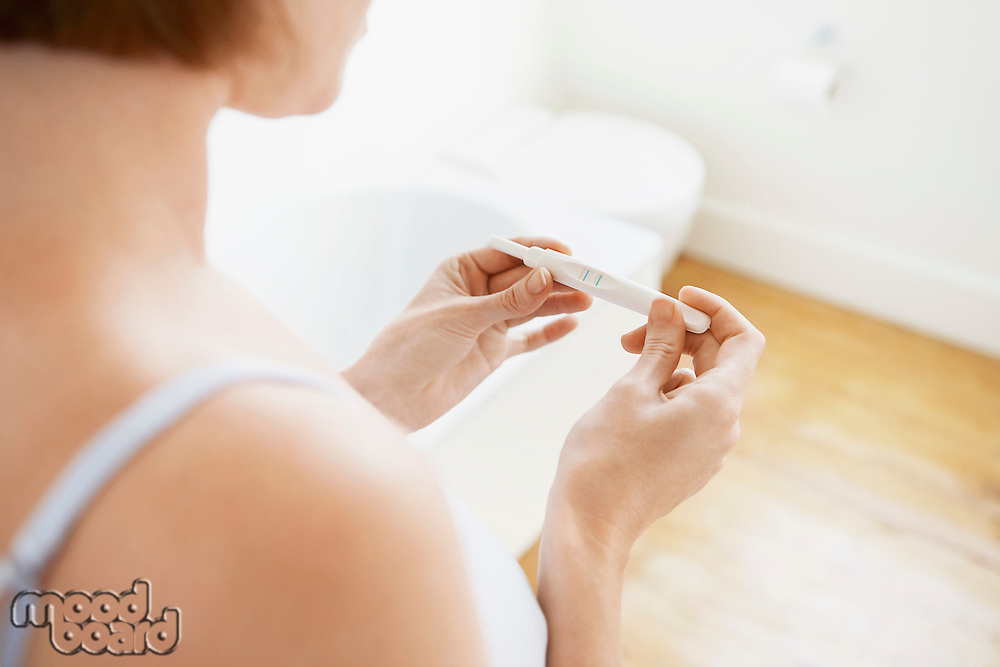 Woman Checking Pregnancy Test Kit mid-section focus on hands