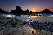 The setting sun creates silhouettes of the Seal Rocks on the Oregon Coast