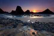 The setting sun creates silhouettes of the Seal Rocks on the Oregon Coast