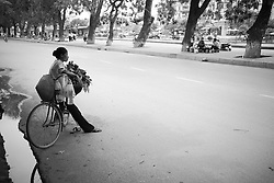 Vietnamese vendor's sitting on bicycle with her goods, Hanoi, Vietnam, Asia.