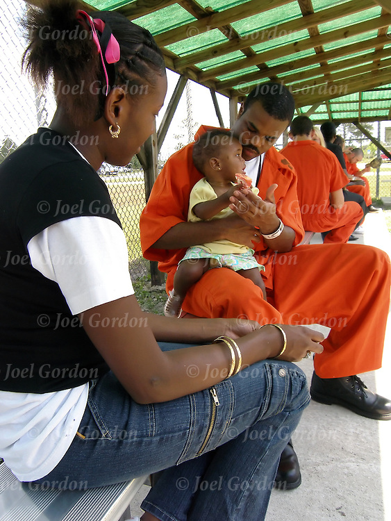 Jail visitation rights - outside in fenced in area - African American trustee in red jump suit being visited by girl friend and 11 month daughter  release 1799 exercise yard, Rec Yard, jail rec yard, jail exercise yard