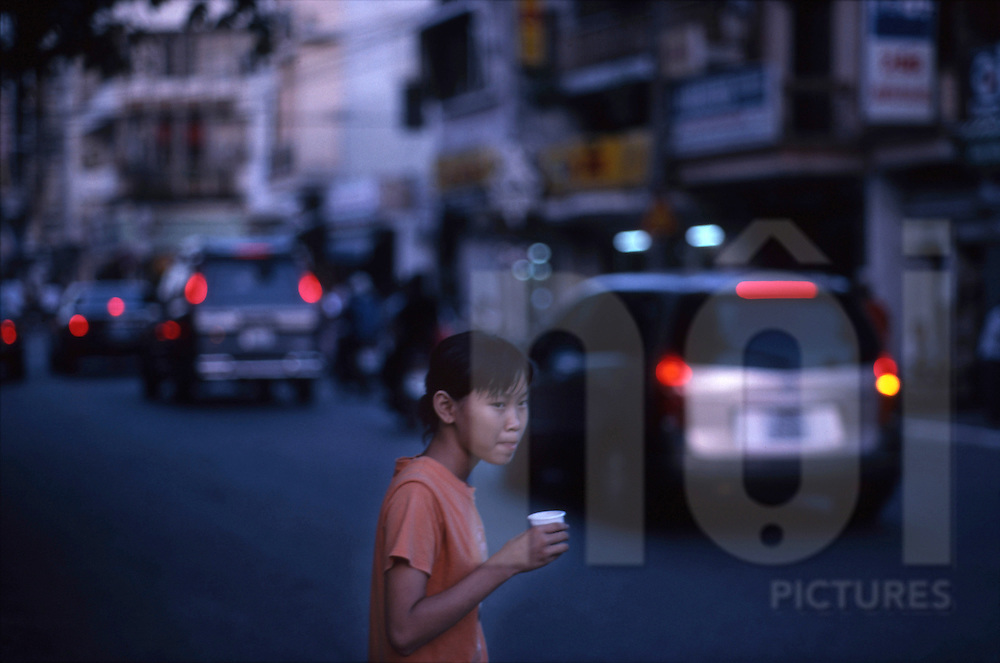 a young girl crosses the street at dusk, in Hanoi Vietnam.