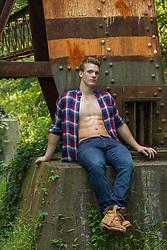 muscular man sitting on a railroad trestle