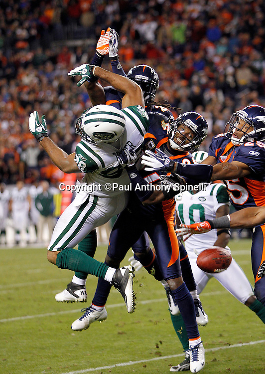 New York Jets wide receiver Patrick Turner (88) leaps for a pass broken up by Denver Broncos cornerback Champ Bailey (24) and Denver Broncos strong safety Chris Harris (25) during the NFL week 11 football game against the Denver Broncos on Thursday, November 17, 2011 in Denver, Colorado. The Broncos won the game 17-13. ©Paul Anthony Spinelli
