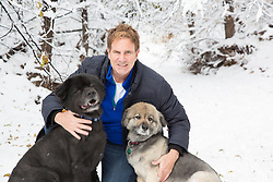 man with two Chow dogs in the snow