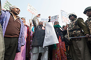 23rd Dec. 2012. A woman raises her hands in the air as riot police keep a close watch in central New Delhi. In the aftermath of the gang-rape of a young medical student, mass protests took place in the capital.