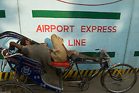 Construction du metro de New Delhi, Inde. Tired worker takes a nap near New Delhi metro construction site.