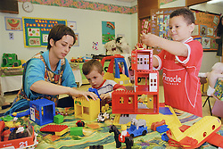 Children with nursery nurse playing with lego in hospital playroom,