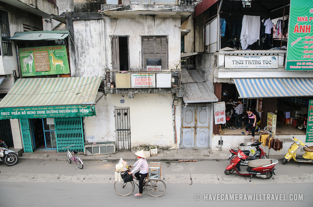 A woman rides a bicycle down a street in Hanoi, Vietnam.