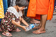 "22 JULY 2013 - PHRA PHUTTHABAT, THAILAND: A girl washes a monk's feet during the Tak Bat Dok Mai at Wat Phra Phutthabat in Saraburi province of Thailand, Monday, July 22. Wat Phra Phutthabat is famous for the way it marks the beginning of Vassa, the three-month annual retreat observed by Theravada monks and nuns. The temple is highly revered in Thailand because it houses a footstep of the Buddha. On the first day of Vassa (or Buddhist Lent) people come to the temple to ""make merit"" and present the monks there with dancing lady ginger flowers, which only bloom in the weeks leading up Vassa. They also present monks with candles and wash their feet. During Vassa, monks and nuns remain inside monasteries and temple grounds, devoting their time to intensive meditation and study. Laypeople support the monastic sangha by bringing food, candles and other offerings to temples. Laypeople also often observe Vassa by giving up something, such as smoking or eating meat. For this reason, westerners sometimes call Vassa the ""Buddhist Lent.""     PHOTO BY JACK KURTZ"