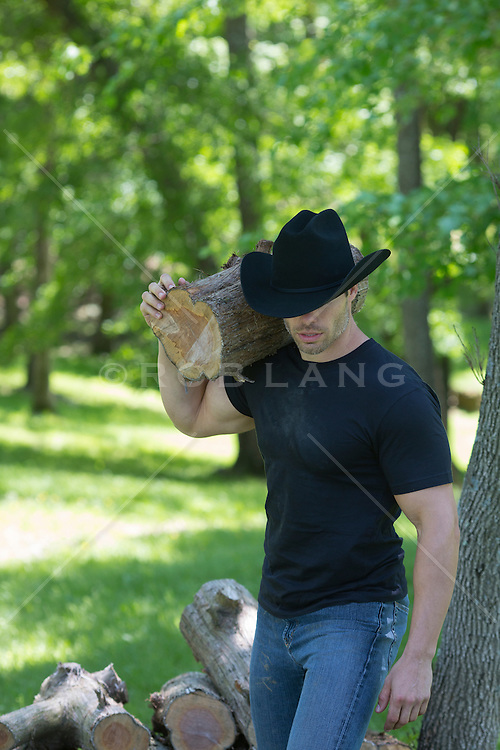 muscular cowboy carrying a log over his shoulder outdoors