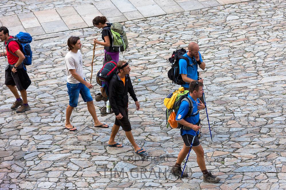 Pilgrims with walking poles end pilgrimage Camino de Santiago in Cathedral square of Santiago de Compostela, Galicia, Spain