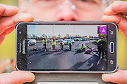 A protestor proudly shows off his images of the action that temporarily blocked the slip road to the M4 -  Protestors block roads on the routes into Heathrow from the M4. Several are arrested.