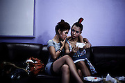 "YANGON, MYANMAR, MARCH 2012: Htike Htike and Ha Moon checking their make-up before a concert.<br /> Burma is a country in Transition. And if that hasn't been made clear enough by the political debates and the recent by-elections, meet the Me N Ma Girls, the first girlband in the country.<br /> The timing couldn't be better. After the April 1st elections in 2012 an always increasing number of investors from all over the world has been visiting Myanmar. After decades of military regime and isolation, the strings of censorship have started loosening up. The government censors in fact for years have banned songs and articles, deleting anything that was seen as ""to provocative"" such as leather outfits and colored wigs.<br /> Describing themselves as Myanmar's first all-girl group, under the management of the Australian dancer and choreographer Nicole May, these five women - coming from either Buddhist or Catholic background and formerly known as Tiger Girls - not only have been challenging censorship laws but they're as well trying to win hearts in a society that in many ways remains man-dominated and socially conservative.<br /> In a country that has been locked up for years, the Me N Ma Girls, embracing western pop culture with skimpy outfits and catchy songs, show with every performance the will of the Burmese youth to come out of a decades-long isolation.<br /> Five girls leading a new form of rebellion: the kind that questions roles and cultural norms."