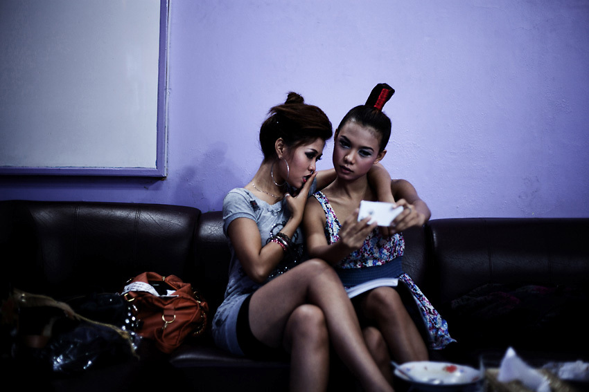 YANGON, MYANMAR, MARCH 2012: Htike Htike and Ha Moon checking their make-up before a concert.<br /> Burma is a country in Transition. And if that hasn't been made clear enough by the political debates and the recent by-elections, meet the Me N Ma Girls, the first girlband in the country.<br /> The timing couldn't be better. After the April 1st elections in 2012 an always increasing number of investors from all over the world has been visiting Myanmar. After decades of military regime and isolation, the strings of censorship have started loosening up. The government censors in fact for years have banned songs and articles, deleting anything that was seen as &quot;to provocative&quot; such as leather outfits and colored wigs.<br /> Describing themselves as Myanmar's first all-girl group, under the management of the Australian dancer and choreographer Nicole May, these five women - coming from either Buddhist or Catholic background and formerly known as Tiger Girls - not only have been challenging censorship laws but they're as well trying to win hearts in a society that in many ways remains man-dominated and socially conservative.<br /> In a country that has been locked up for years, the Me N Ma Girls, embracing western pop culture with skimpy outfits and catchy songs, show with every performance the will of the Burmese youth to come out of a decades-long isolation.<br /> Five girls leading a new form of rebellion: the kind that questions roles and cultural norms.