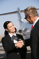 Mid-adult flight attendant and senior businessman shaking hands.