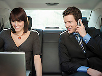 Mid adult woman and businessman sitting at back seat of car using mobile phone and laptop