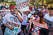 25 JUNE 2012 - PHOENIX, AZ:   ORLANDO ARENAS (left) and ERIKA OVALLE lead chants in front of the Immigration and Customs Enforcement (ICE) offices in central Phoenix Monday. About 100 immigration supporters held a protest against ICE and continued deportations by the Obama administration. Protesters also celebrated the US Supreme Court decision to overturn most of SB1070, Arizona's tough anti-immigration law.    PHOTO BY JACK KURTZ