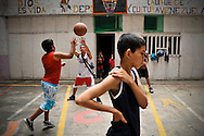 "Boys play basketball as part of a sports program organized by the ""Tower of David"" community council to keep children living in the skyscraper out of trouble."
