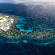 Aerial Panorama of Lualoli Island in the Vava'u island group of the Kingdom of Tonga, showing the extensive fringing reef that extends far off one end, with additional submerged reef nearby.